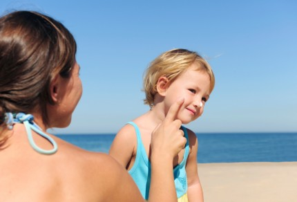Suncare on the beach: Mother applying suntan lotion to her daughter